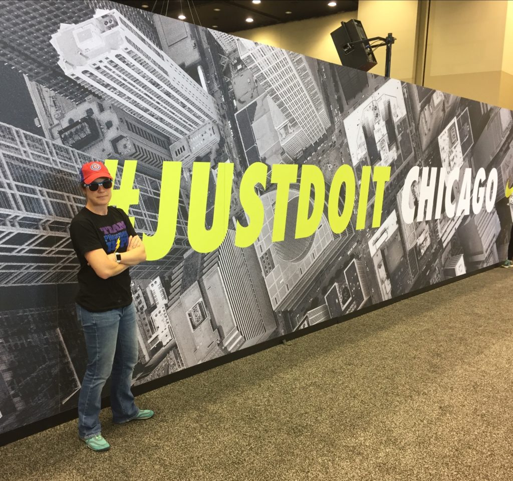 PG at the marathon expo, posing in front of the Just Do It sign