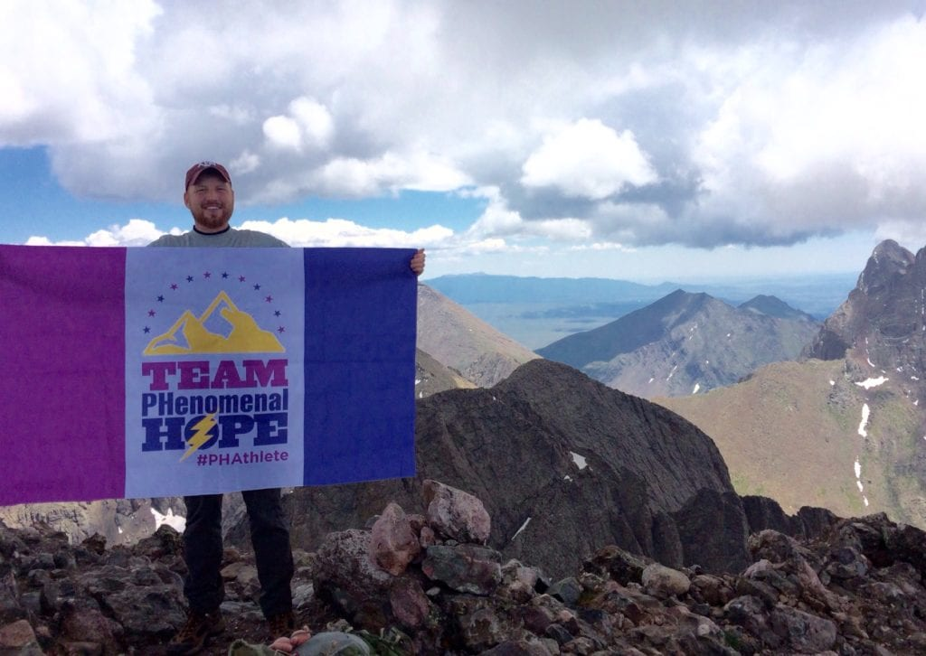 Shelby Anders with a Team PHenomenal Hope flag on top of a 14,000' mountain