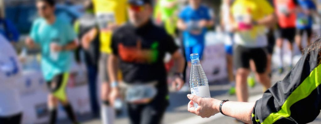 a volunteer handing out water during a footrace