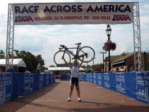 Sara Harper Raising her bicycle above her head at the 2014 RAAM finish line
