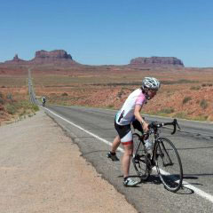 Sara Harper getting on her bicycle on a desert road