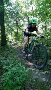 Sara Harper bicycle racing through the woods