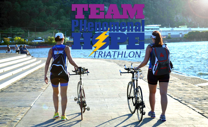 Image of Monica Reisz and Amanda Budzowski walking with their bicycles at Point State Park, Pittsburgh, PA