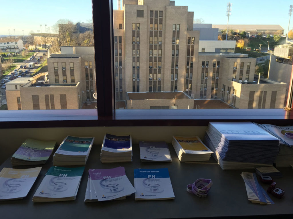 a view from a window at UPMC/Pitt behind stacks of literature on pulmonary hypertension
