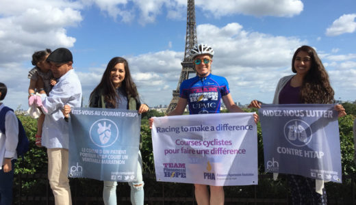 Patty George and friends holding signs in front of the Eiffel Tower in Prais in 2015