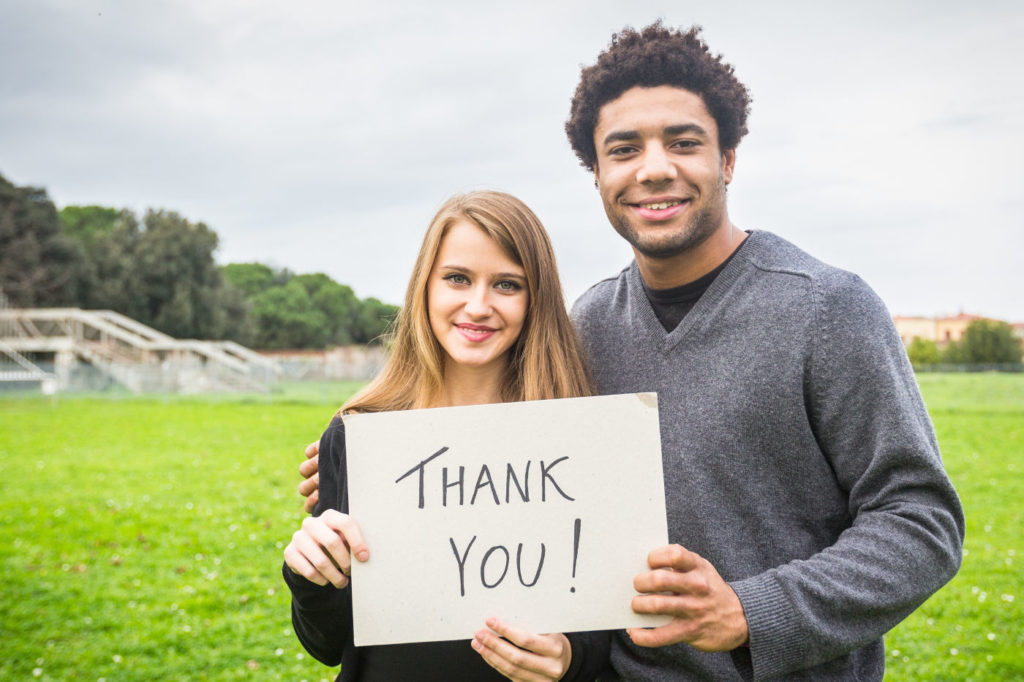 Two people outside in a green field who are holding a sign that says Thank You
