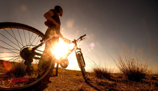 A cyclist standing by a bike with the low sun in the distance