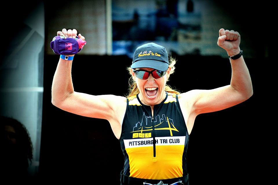 vicki dolan with her hands raised in victory during a race