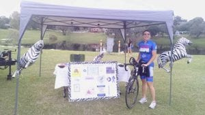 Kathleen Richardson with informational tent and zebras