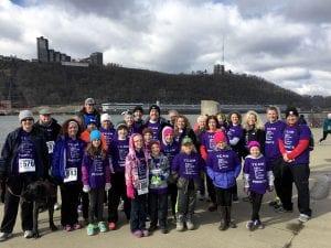 A team of racers all wearing purple jerseys