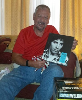 Dan in December 2015, holding up an album of his favorite artist, Bruce Springsteen