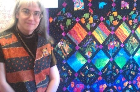 Diane Kowalik standing in front of a beautiful quilt