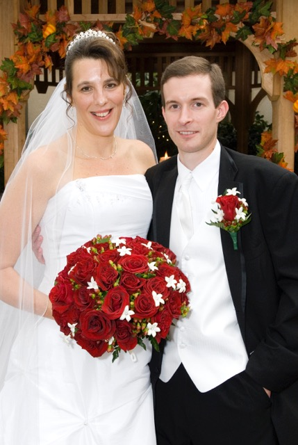 Diane on her wedding day next to her husband with a beautiful red bouquet