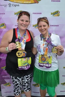 Beth Hamilton smiling with friend and race medals