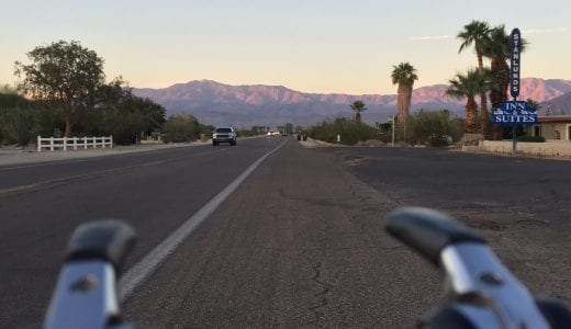 view of the road ahead from the perspective of cycling handlebars